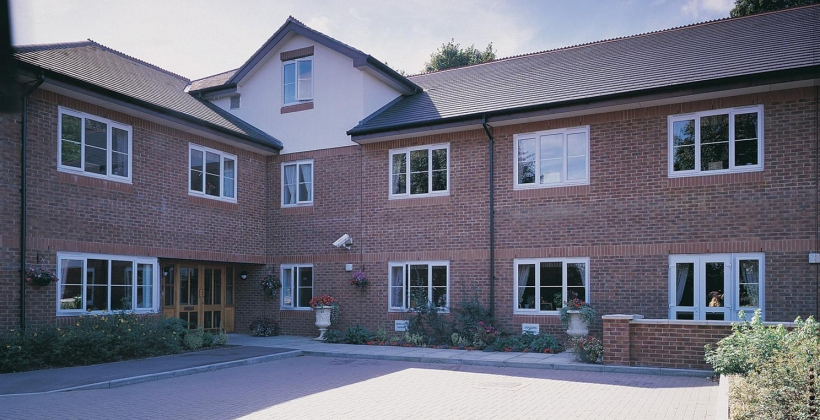 Front view of Shelburne Lodge Care Home which is surrounded by flower beds and potted plants