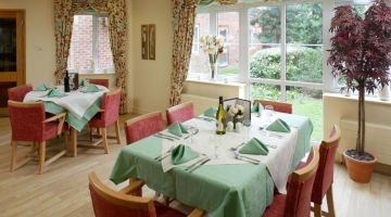 A dining room with two tables with a view of the garden