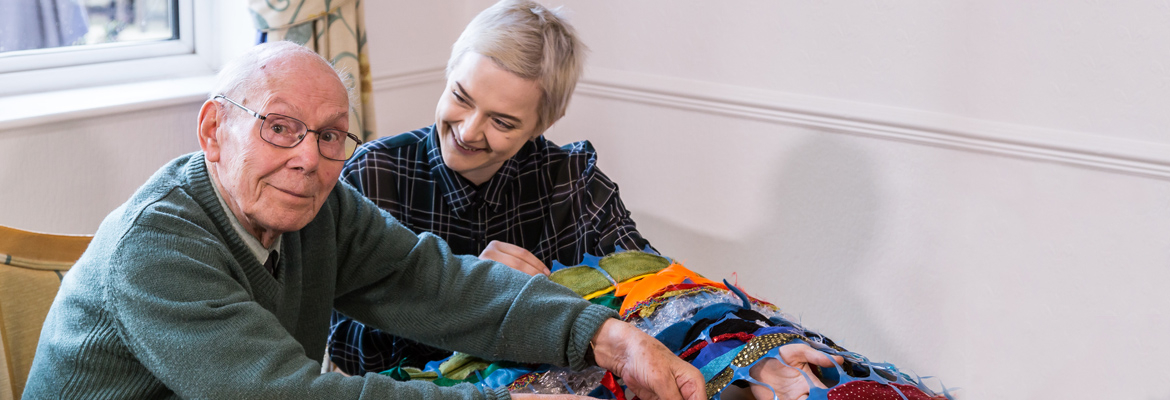 A volunteer helping a resident at Barchester Healthcare