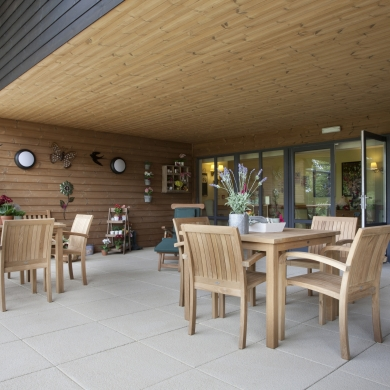 Wooden tables and chairs on a patio with a roof