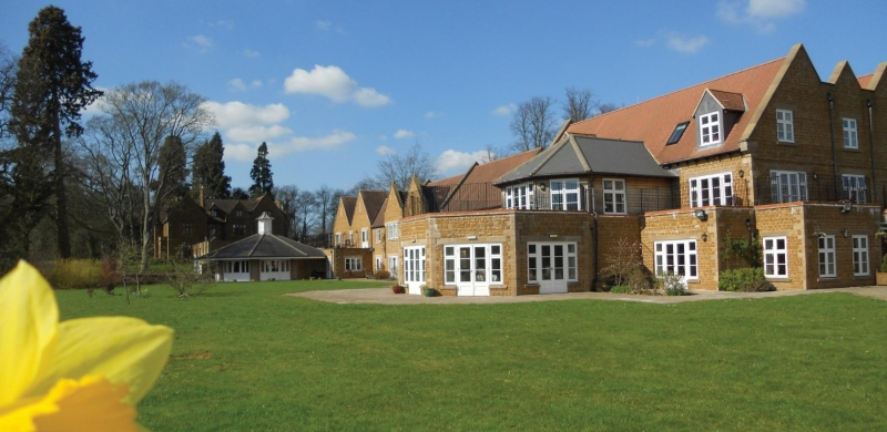 A view of the Chacombe Park grounds; a large building surrounded by green grass