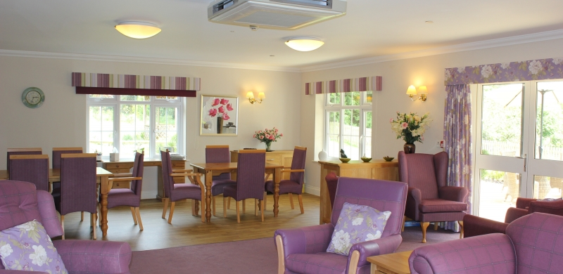 Large room filled with purple armchairs and wooden tables