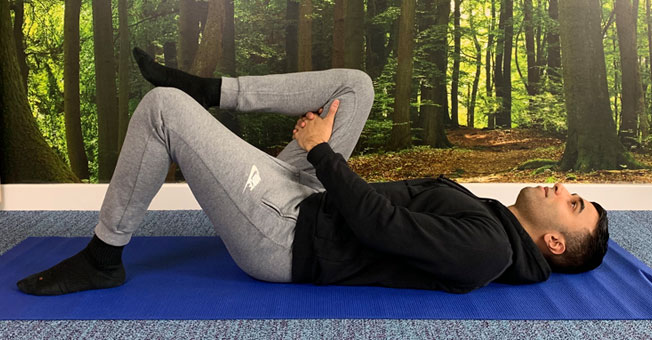 Yoga pose, knee to chest.