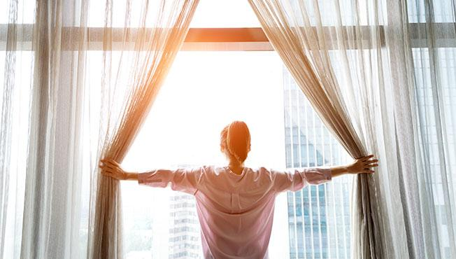 Woman opening curtains and looking out.