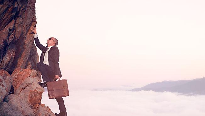 Man wearing a suit and climbing up rocks.