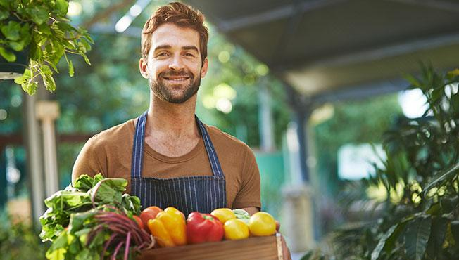 Happy man holding box of fruit and vegetables