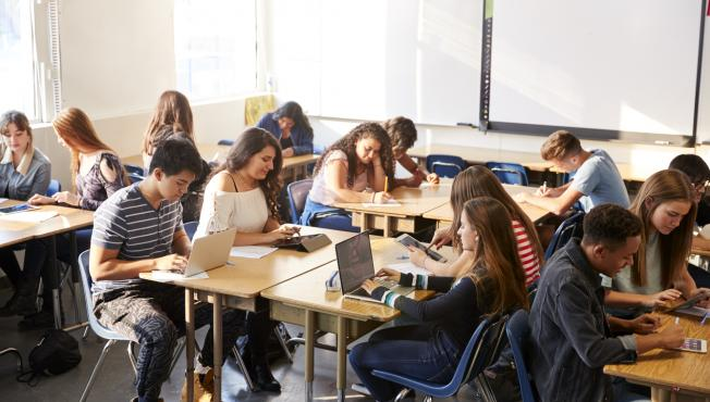 A class room of teenagers sitting at tables and working