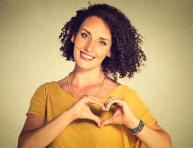 Smiling cheerful woman making heart sign with hands