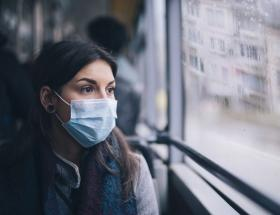 woman wearing facemask on a bus