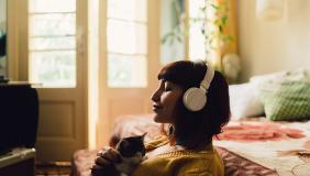 Woman wearing headphones, taking a moment with a cat