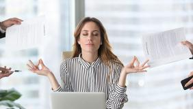 Calm female executive meditating taking break avoiding stressful job