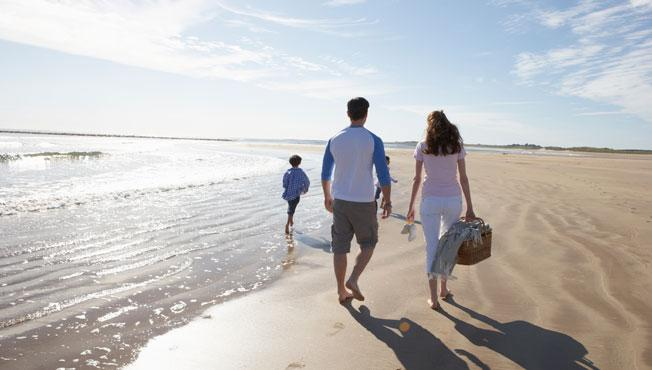 Family going for walk at the beach.