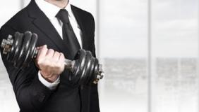 Man in suit lifting dumbbell