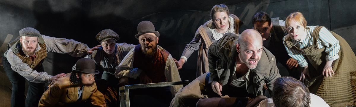 Dickensian characters in the Great Expectations ensemble pursue and crowd round Pip