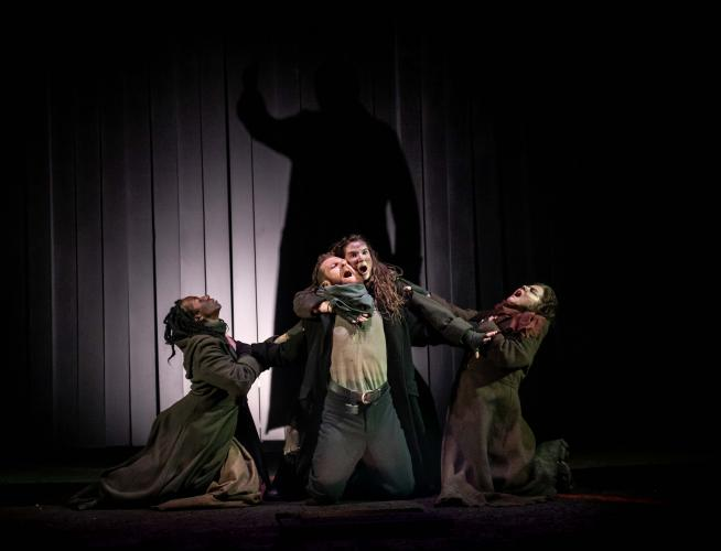 A kneeling man grasped by three screaming women, while a silhouette looms behind.
