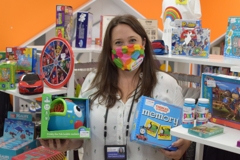 A lady wearing a colour face mask, holding two boxes of toys