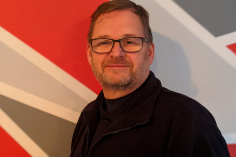 A man standing against a red wall in a dark jumper