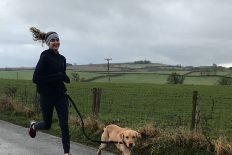 A female runner in all black running with a dog