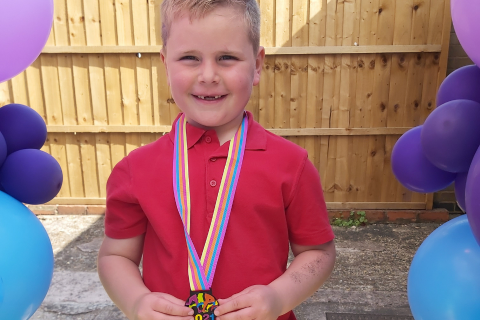 A young boy wearing a red tshirt with a medal around his neck