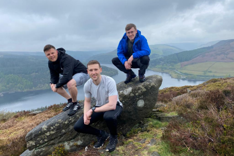 Three young men squatting at the top of a mountain