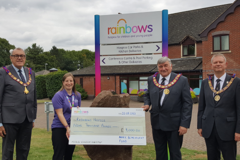 Two people standing with a big cheque outside Rainbows Hospice for Children and Young People