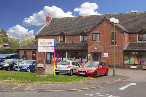 Outside Rainbows Hospice for Children and Young People on a sunny day with cars in the car park