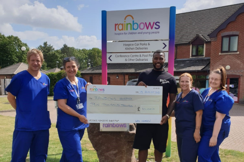 Wes Morgan and a group of nurses holding a big cheque at Rainbows