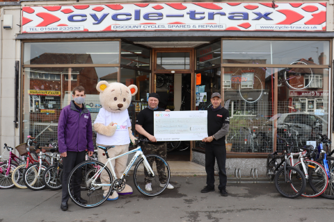 Three men standing with a big cheque and a bike, alongside mascot Bow Bear
