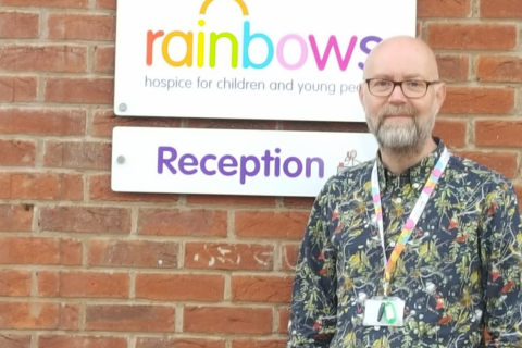 A man standing against a wall, with the Rainbows Hospice sign in the background