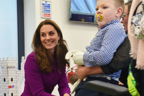 Kate Middleton kneeling infront of a young boy in a wheelchair