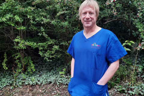 A male nurse in blue scrubs standing with hands in pockets