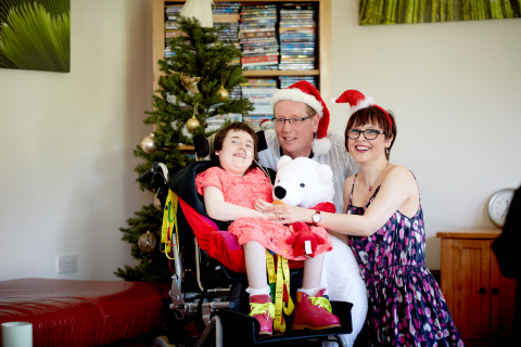 A young girl in a pink dress sat in a wheelchair with a polarbear soft toy and her mum and dad next to her