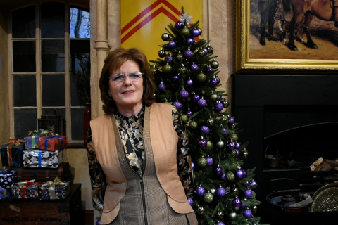 The Duchess of Rutland standing infront of a Christmas tree