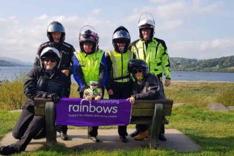 Motorcyclists with a Rainbows sign