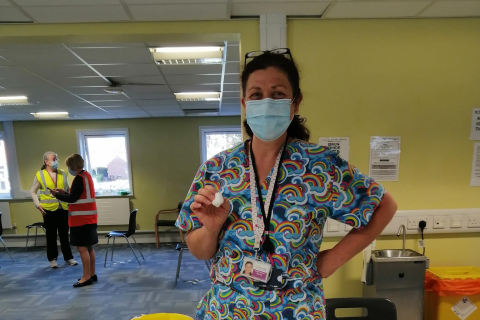 A female nurse in scrubs and a face mask looking at the camera