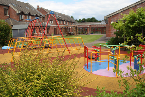 Swings and a roundabout in the garden at Rainbows Hospice